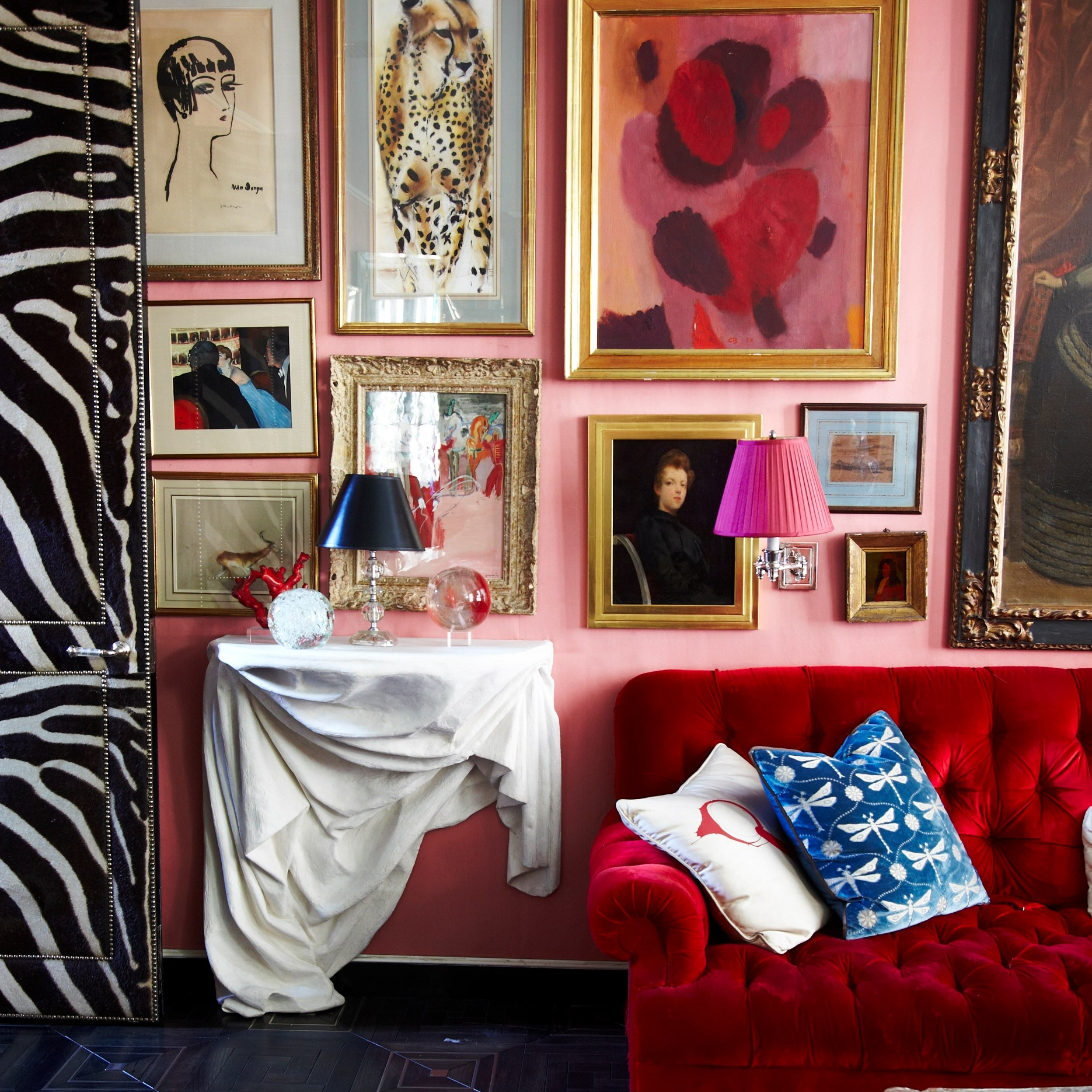 red couch in pink room with zebra wall