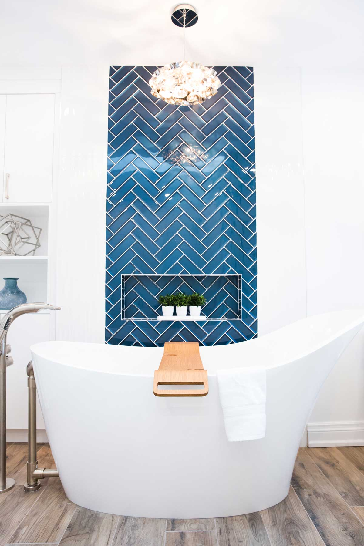 standalone bathtub with blue herrinbone tile