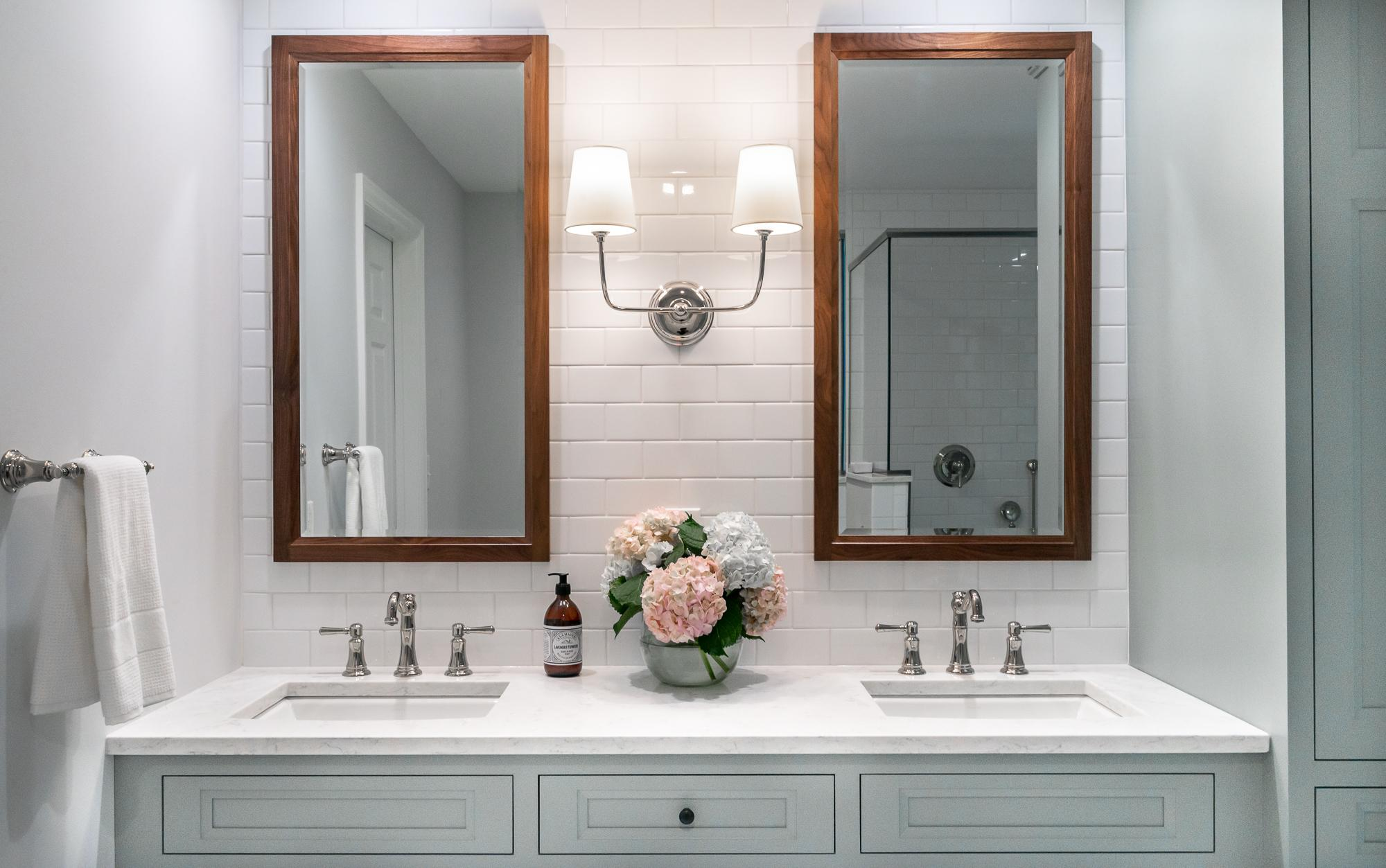 Bathroom with white tile, teal cabinets, and duel mirrors