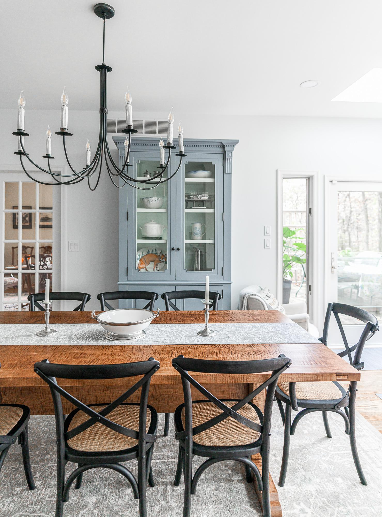 Wooden dining room table with chandelier and teal china cabinet