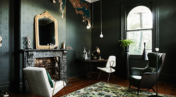 emerald green living room featuring painted walls and gold mirror